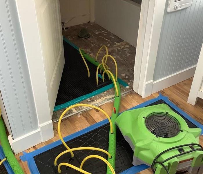 Water damage in a bathroom in Flagstaff, AZ, with our specialty drying equipment that we use for hardwood floors