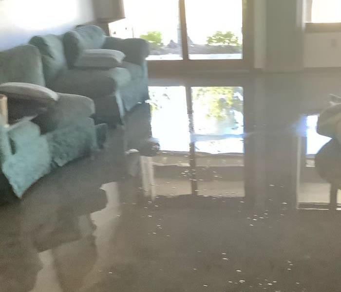 A floor in Flagstaff, Arizona that has standing water on it. There also two green chairs that have been soaked