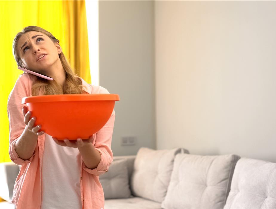 woman on cell phone holding orange bucket looking up at leaky ceiling