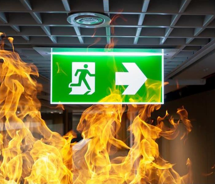 a green exit sign surrounded by flames